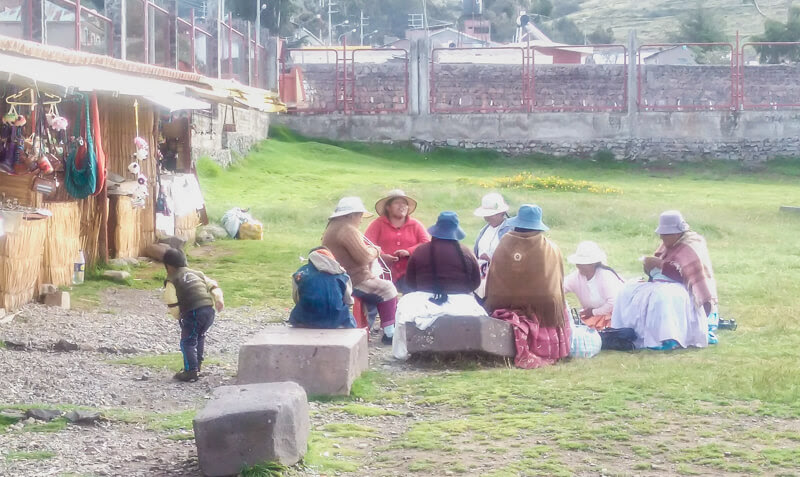 peruvian and quechua and aymara women weaving and sitting in a group in puno lago titicaca peru latin america