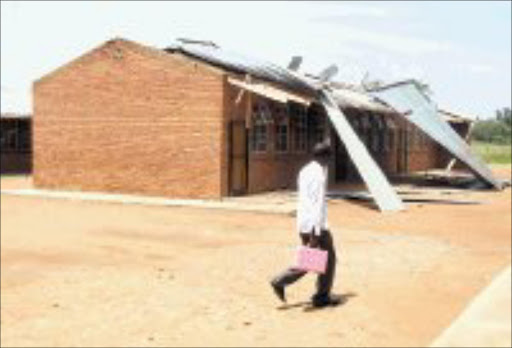 DEVASTATION: A pupil walks on the grounds of Lebowakgomo Secondary School in Limpopo. The school was damaged by a storm at the weekend. Pic. Edward Maahlamela. 16/01/07. © Sowetan.
