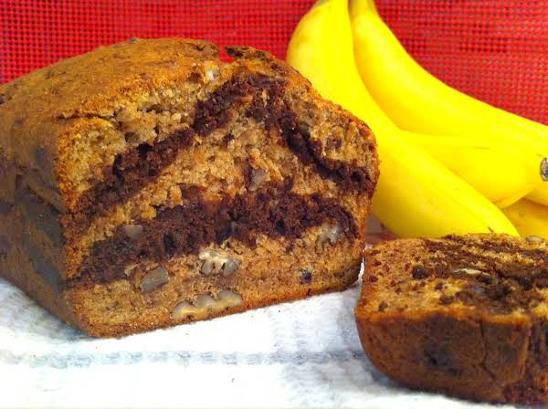 A Loaf Of Banana Bread Sitting On A Dish Towel With A Bunch Of Bananas In The Background.