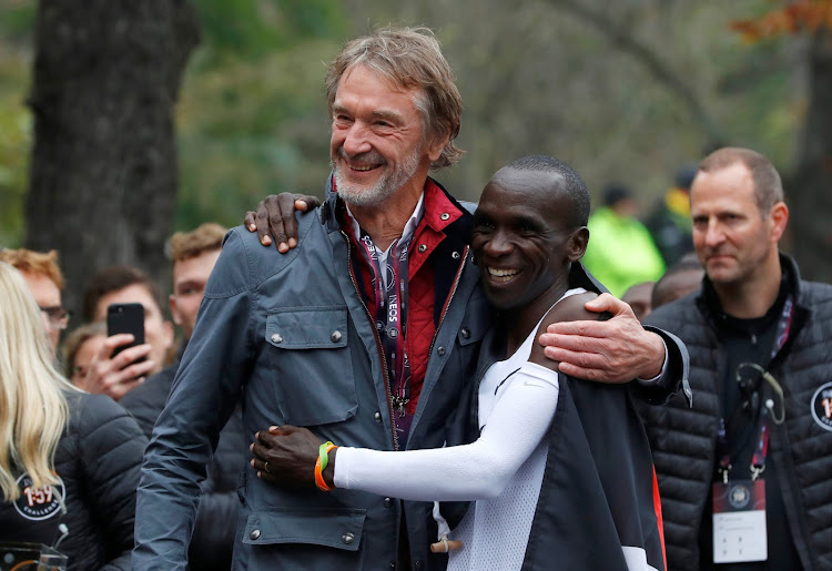 Eliud Kipchoge, the marathon world record holder, is congratulated by the CEO of the Ineos chemicals group Jim Ratcliffe, after a successful attempt to run a marathon in under two hours in Vienna, Austria, October 12, 2019.