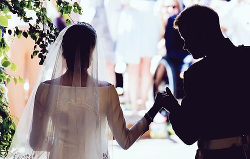 Meghan and Harry walk hand in hand, silhouetted from the back against a naturally lit background.
