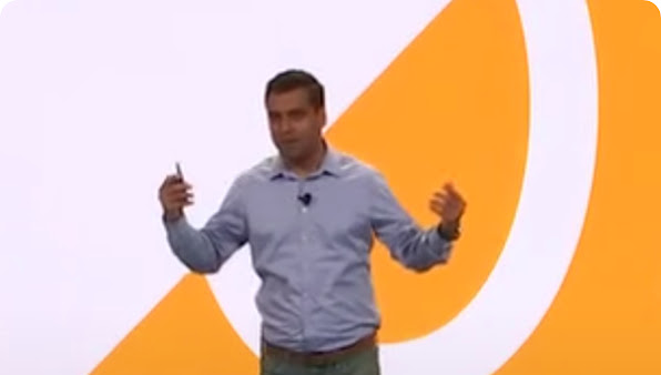 Man in gray shirt gestures expressively while presenting onstage