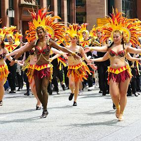 carnival dancers by Yvonne Katcher - City,  Street & Park  Street Scenes ( headgear, orange, street, road, yellow, people )