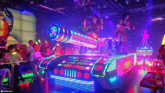 Japanese girls & neon lit tanks while enjoying dinner at the Robot Restaurant in Kabukicho, Tokyo, Japan