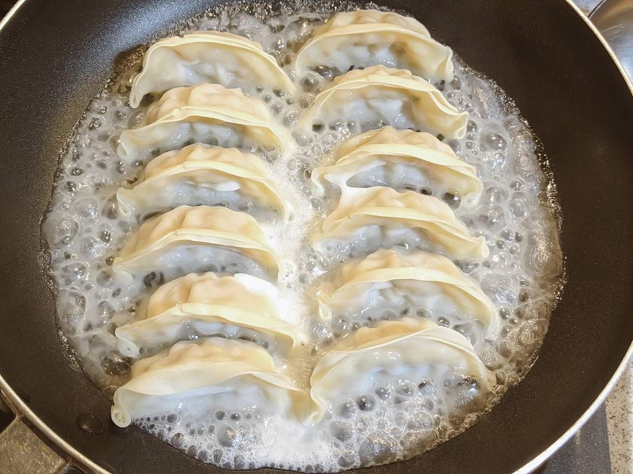 大阪王将餃子をフライパンで焼いている画像 羽根のところが円状になり沸騰して泡立っている