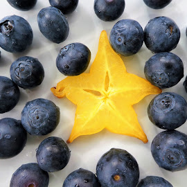 A yellow passion fruit star among the blueberries by Svetlana Saenkova - Food & Drink Fruits & Vegetables ( close up, yellow star, star, blueberries, yellow fruit, breakfast )