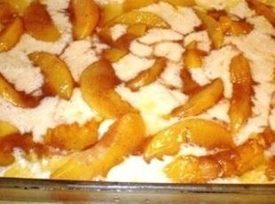 Using a slotted spoon, scoop out peach slices and place into batter, spreading all...