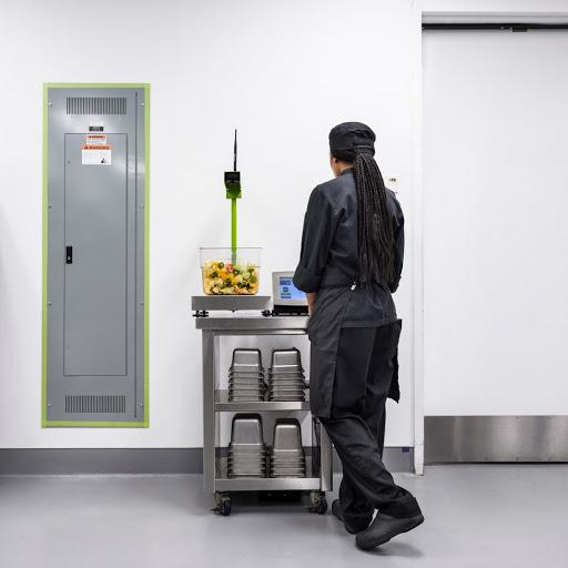 Rückansicht einer Person, die schwarze Berufsbekleidung trägt und Lebensmittel auf einem grauen Metallwagen wiegt