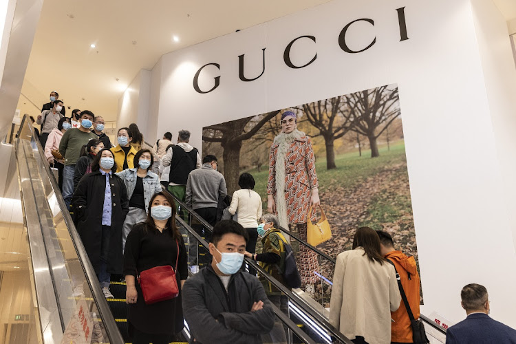 Customers ride escalators in front of Gucci billboard in Wuhan, Hubei Province, China, March 25 2021. Picture: GETTY IMAGES