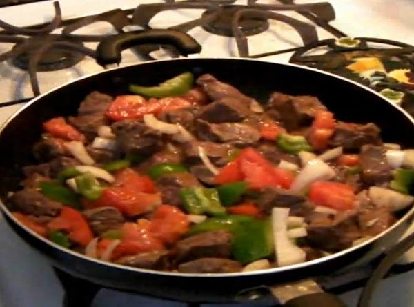 Garlic and spices added to pan with meat, onion, peppers, and tomatoes.