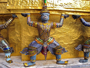 Photo: giant holding up gold chedi