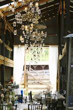 Photo: Hay Barn- reception site with custom wagon wheel and mason jar chandeliers Dana Romanoff Photography