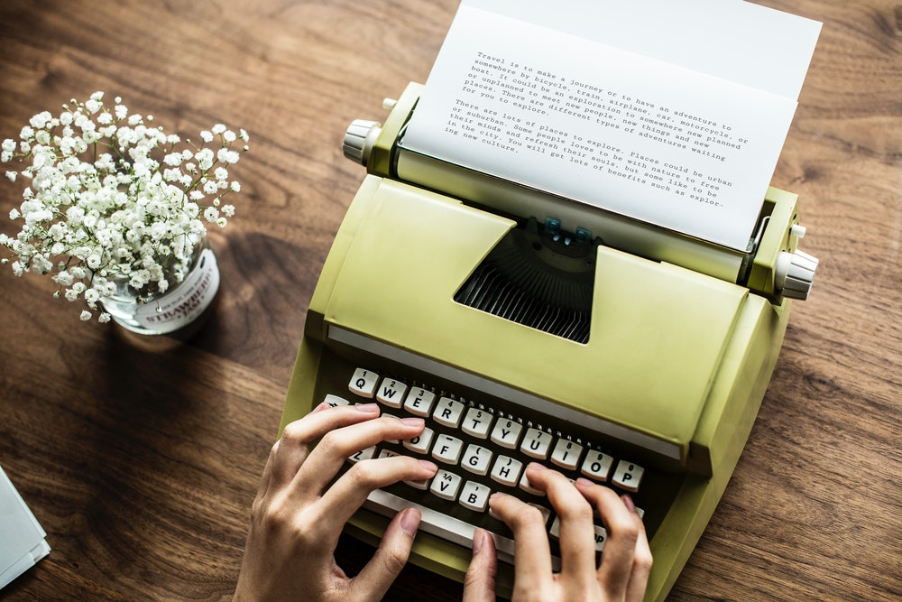 person typing on brown typewriter