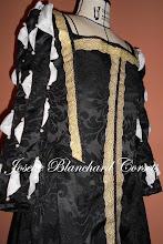 Photo: Vestido Dinastia Tudor em brocado preto com aplicação de gorgorões e rendas. Com corset embutido, manga com detalhe de camisa branca e pérolas. Aberturas laterais com fechamento por ilhóses nas abertura, com protetor embutido, forro 100% algodão, calda na saia. A partir de R$ 600,00. CADA MODELO É ÚNICO E POSSUI ACABAMENTO EXCLUSIVO.