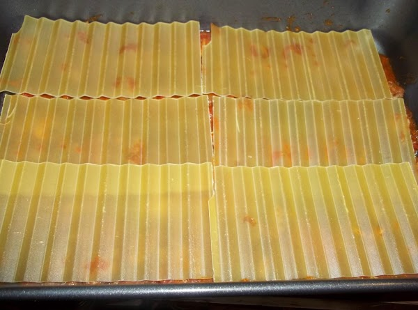 Lay lasagna noodles on top of the sauce. Making sure you cover the sauce,...