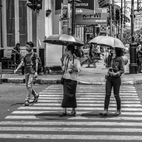 crossing by Tonny Haryanto - City,  Street & Park  Street Scenes ( crosswalk, crossing, girls, walking, ladies, rainy day, braga, umbrella, street, cebra cross, people, bandung, street photography, two, umbrellas, indonesia, west java )
