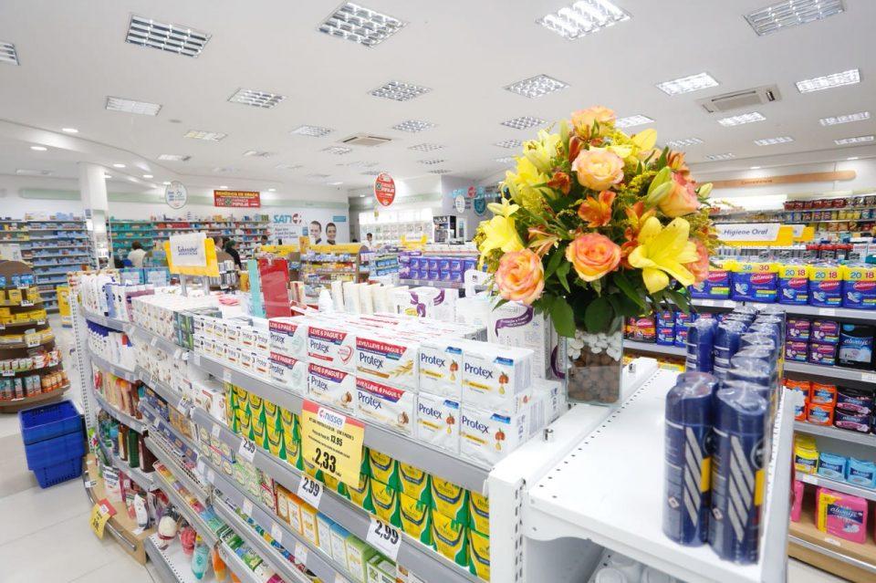 A imagem mostra uma gôndola de farmácia com um vaso de flores em cima. Detalhe que pode ser interessante quando se pensa em como organizar uma farmácia.