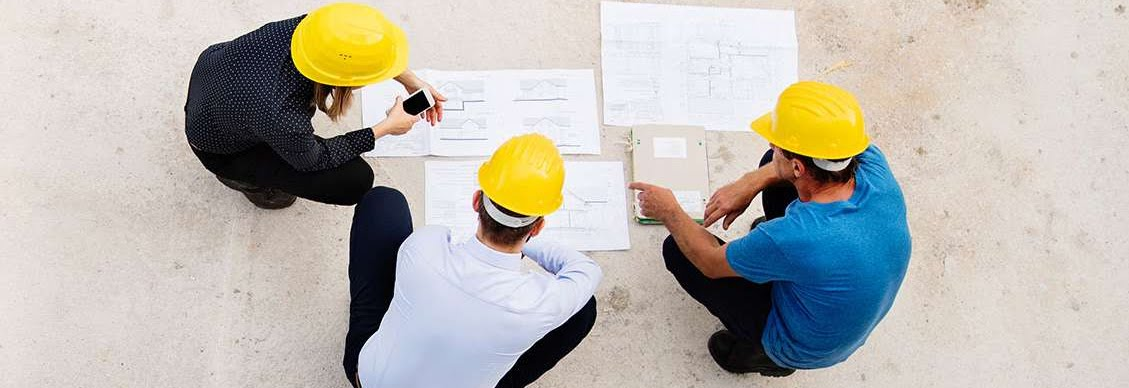 three contractors looking at building blueprints on the floor