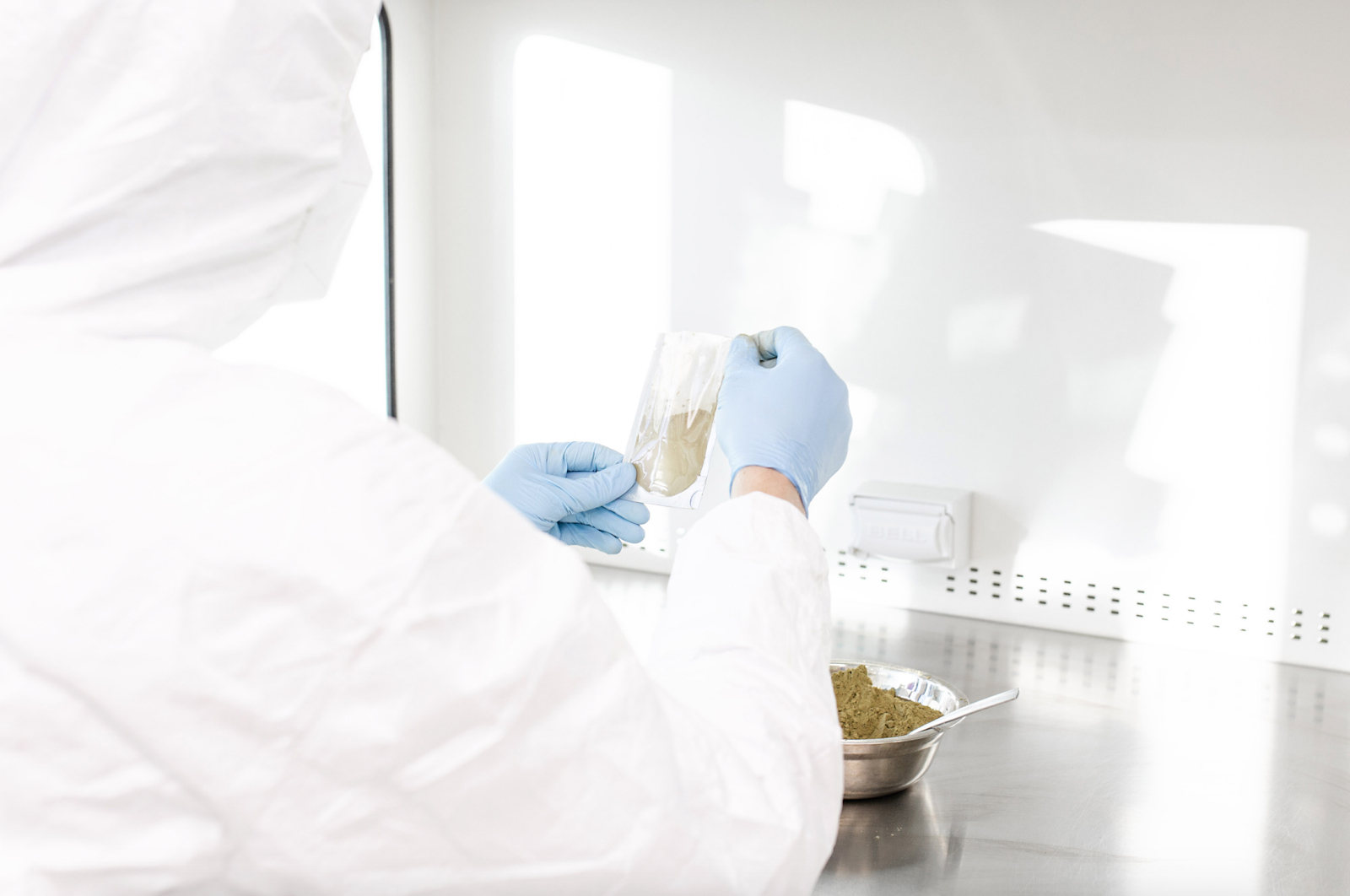 Image of Happy Hippo production lab worker filling a 1oz packet of kratom powder