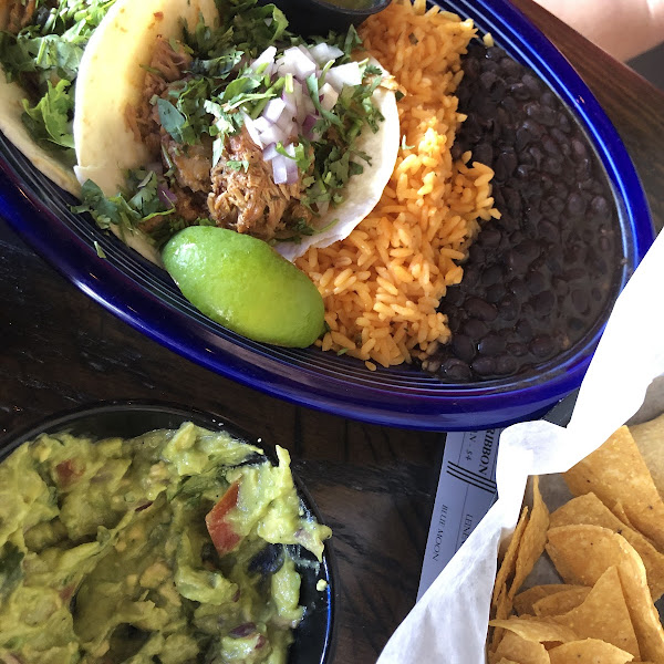 Guacamole and chips. Those are the mexican street tacos on the blue plate!