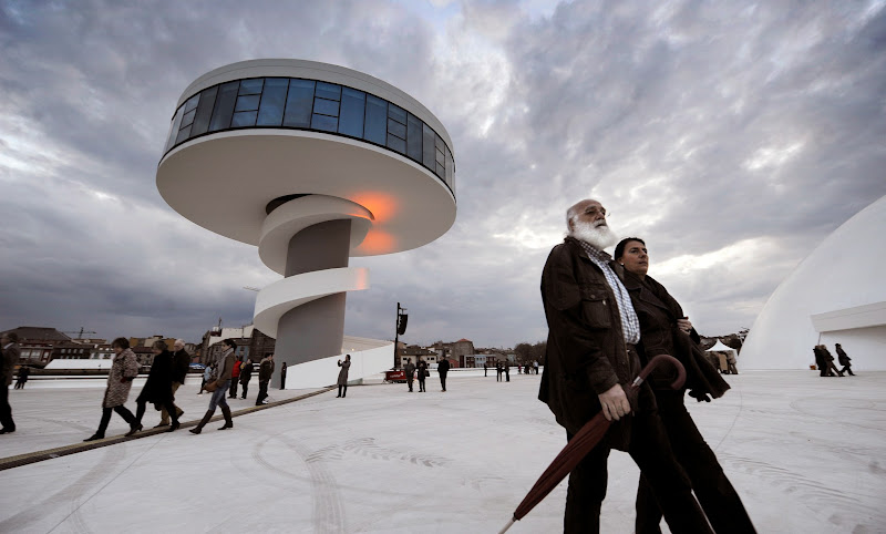 Photo: (FILES) This file picture shows people walking next to one of the buildings of the Niemeyer Center, during the cultural center opening, on March 25, 2011, in the Spanish northern city of Aviles. The Niemeyer Center, designed by 103-year-old Brazilian architect Oscar Niemeyer, could be closing just six months after it opened, as Spain is currently experiencing an economic slump. AFP PHOTO / RAFA RIVAS (Photo credit should read RAFA RIVAS/AFP/Getty Images)