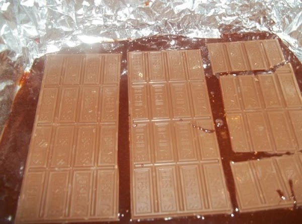 Spread 1/2 the batter evenly into prepared pan. Arrange candy bars in single layer,...