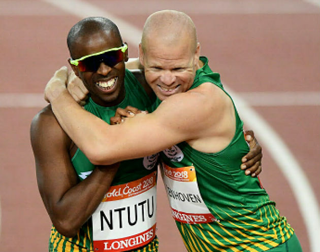 Ndodomzi Jonathan Ntutu celebrates winning gold with silver medallist Hilton Langenhoven in the men's T12 100m final at the Commonwealth Games in Gold Coast, Australia