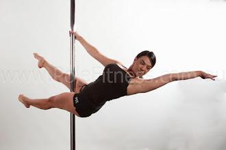 Photo: Vertical Pole Gymnastics - One Handed Scissor Layout