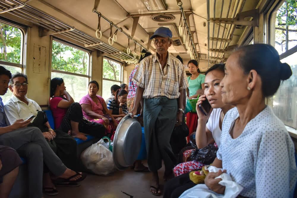 burmese man standing in yangon train in burma