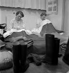 2 op veldbedden zittende en schrijvende vrouwen in een opvang