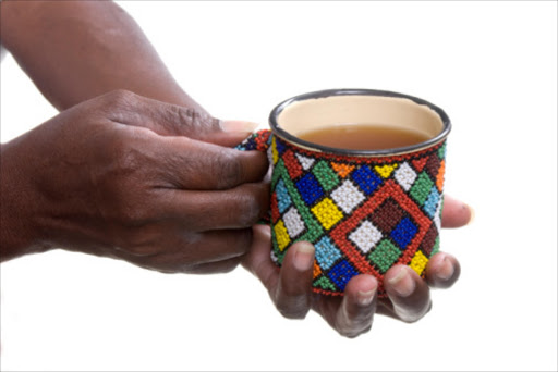 An African woman holding a mug decorated in Xhosa style beads. File photo.