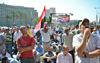 Photo: A large crowd listens with full attention to the speakers on the stage.