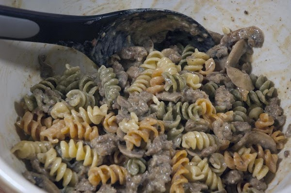Add the skillet ingredients to the bowl containing the pasta, and then stir to...