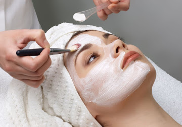 Lady having facial mask applied