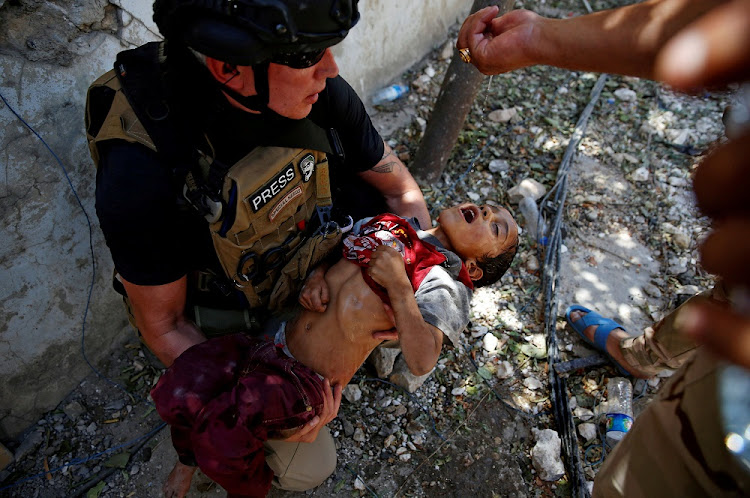 An Iraqi soldier gives water to a dehydrated child rescued during the ongoing fighting near the Old City in Mosul, Iraq, last week. Picture: REUTERS