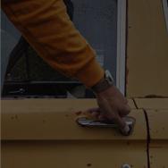 Man's hand on the door handle of a car