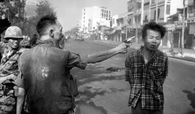 Soldier pointing gun at head of prisoner during Vietnam War