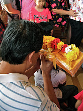 Photo: worshipper offering flowers and golden robes, Wat Traimitr