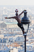 Photo: This is a street performer in Paris by the name of Iya Traore. He was a professional footballer but due to other commitments he dropped out of the professional leagues and decided to make a living from showcasing his talents on the streets instead. We saw him at the foot of the Sacre Coeur, where he has a well honed and impressive routine. It's so good in fact that we watched it several times through!  Note that in the photo below, he didn't just climb the lamp-post then balance the ball on his head to pose for the photo. Rather, he climbed up the post with the ball balanced on his head the whole time, performing a few acrobatic feats along the way!  If you're interested in more information about Iya, you can find his website here: http://www.iya.fr/en/iya_traore.php You can also find video clips of his routine that people have uploaded to YouTube. [Edit: it looks like +Iya TRAORE has a profile on Google+ too!]  Have a great weekend everyone!  #FrenchFriday , curated by +Peak Ness and +Noze P.