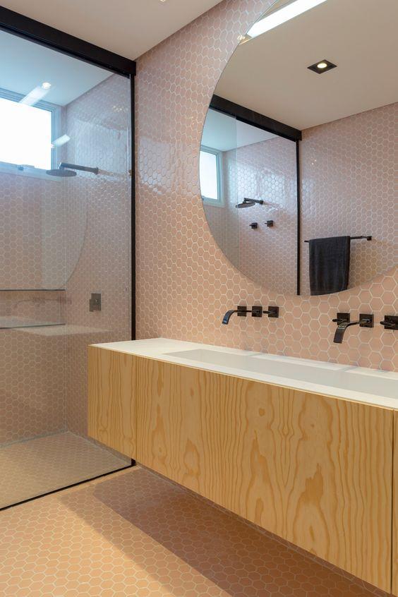 Banheiro revestido nas paredes e piso com revestimento hexagonal rosa, armário de madeira com bancada branca, torneira preta e box de vidro com moldura preta.