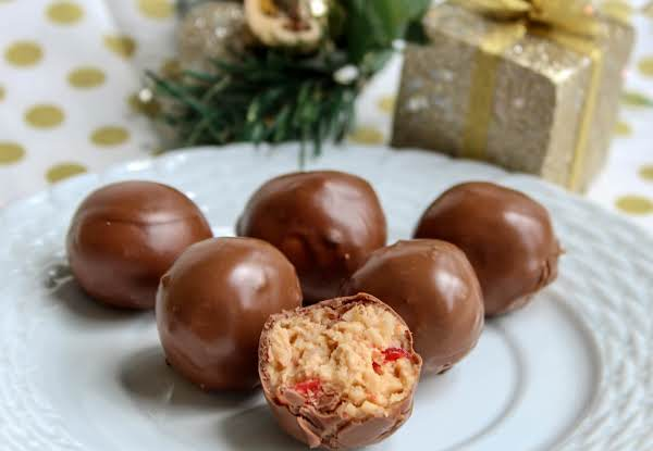 Christmas Peanut Butter Coconut Cherry Balls On A White Plate.