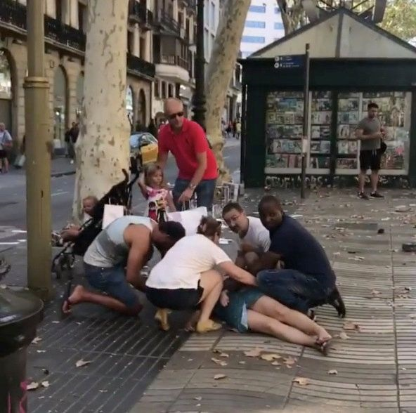 People help an injured woman lying on the ground after a van crashed into pedestrians in central Barcelona, Spain, on Thursday. Picture: REUTERS