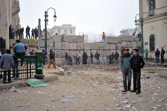 Photo: People assemble outside the wall erected by the army in an effort to put a stop to the ongoing clashes. Many of the protesters claim the purpose of the pre-dawn attack was to provide the army cover while the wall was reinforced with another layer of boulders.