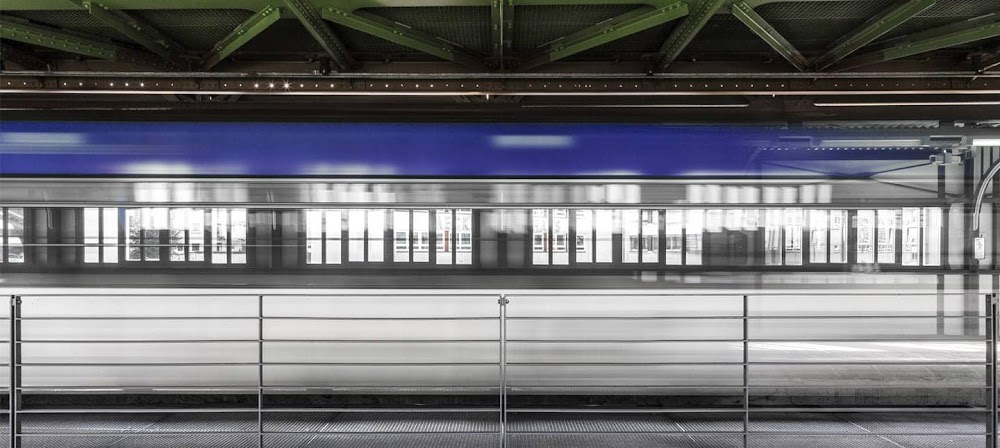 Photograph of a blue and white train in motion inside a train station