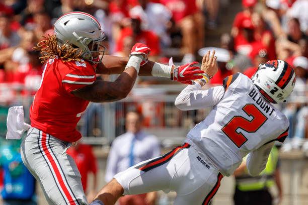 Defensive end Chase Young of the Ohio State Buckeyes knocks quarterback Conor Blount of the Oregon State Beavers off his feet in a game between the...