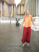 Photo: Doreen Wolff mit einem Tempelwächter im Hintergrund im Königspalast von Bangkok bei einem plötzlichen Regenschauer