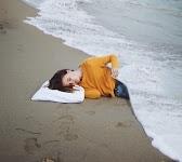 vrouw ligt op strand met de zee als deken