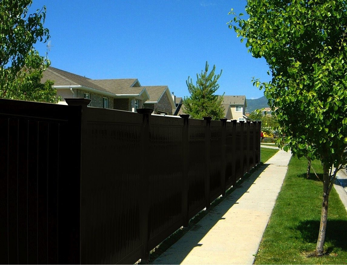 One of Blackline hhp's black vinyl privacy fences installed in a customer's front yard along a sidewalk.
