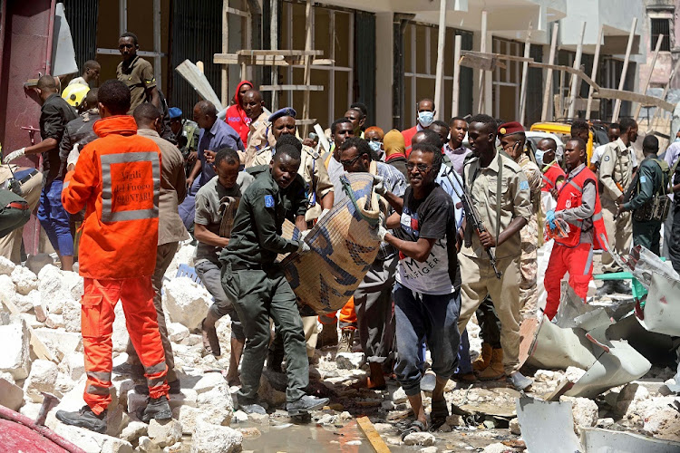 Somali security forces and emergency services evacuate an injured man from the scene where a car bomb exploded at a shopping mall in Mogadishu, Somalia, February 4 2019. Picture: REUTERS/FEISAL OMAR