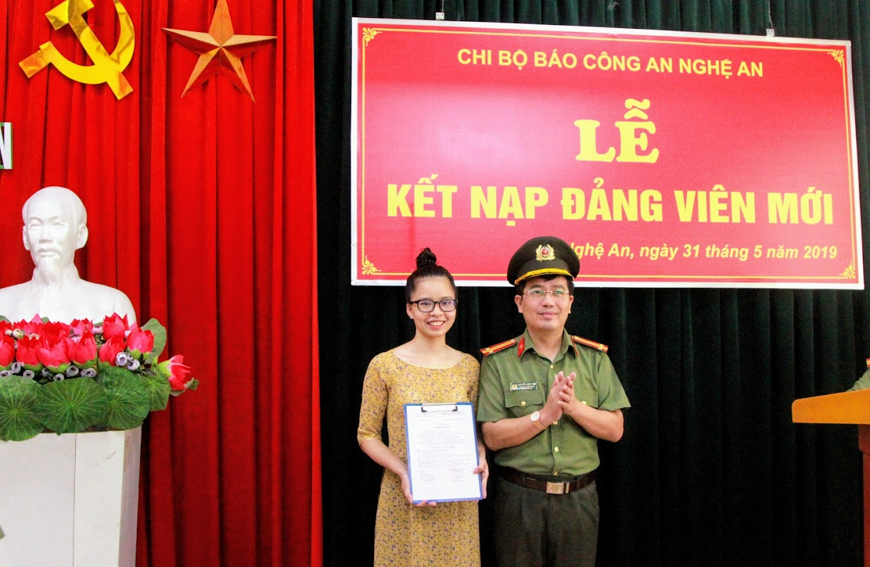 Trung tá Nguyễn Xuân Thư - Bí thư Chi bộ Báo Công an Nghệ An trao quyết định kết nạp  đảng viên mới cho quần chúng ưu tú Hoàng Thị Ngọc Anh.